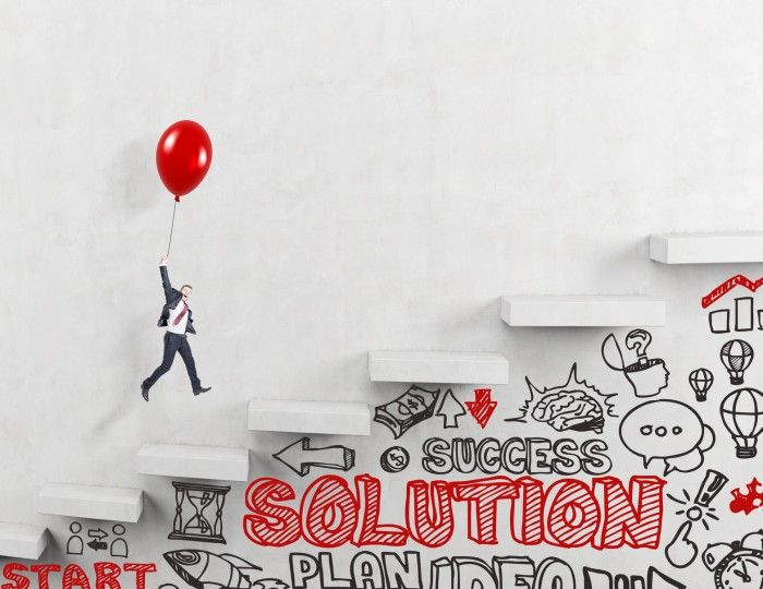 Businessman flying upstairs on red balloon, business icons and words under it. Concrete background.